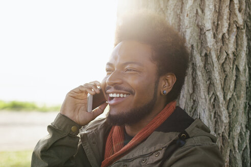 Portrait of smiling young man leaning against tree trunk telephoning with smartphone - EBSF001057
