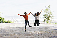 Spain, Barcelona, portrait of happy young couple jumping in the air on view terrace - EBSF001066