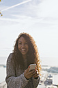 Spain, Barcelona, portrait of smiling young woman with smartphone  at backlight - EBSF001075