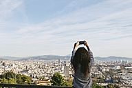 Spain, Barcelona, back view of young woman taking a picture of view with her smartphone - EBSF001078