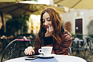 Woman having a coffee outdoors in a little bar - GIOF000478