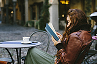 Woman reading a book outdoors in a little bar - GIOF000481