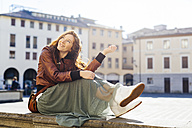 Italy, Padua, woman sitting outdoors at town square - GIOF000487