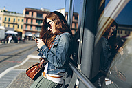 Italy, Padua, woman at the bus stop holding a cell phone - GIOF000505