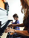Woman and little girl playing piano together - MGOF001049