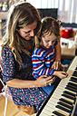 Woman and little girl playing piano together - MGOF001052