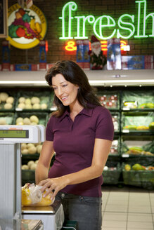 Portrait of smiling customer weighing vegetables in a supermarket - RMAF000219
