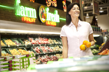 Portrait of smiling customer with three oranges in a supermarket - RMAF000222