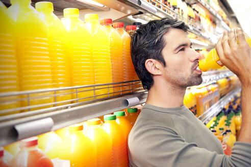Man drinking a bottle of orange juice  in front of fridge in a supermarket - RMAF000225