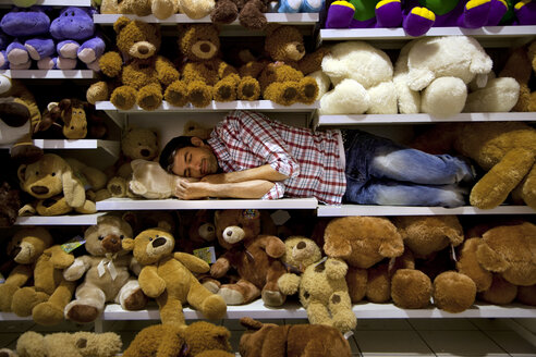 Man sleeping on a shelf between soft toys in a supermarket - RMAF000228