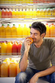 Portrait of smiling man sitting in front of fridge with rows of juice bottles in a supermarket smelling orange - RMAF000231
