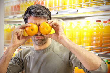Man in front of fridge with rows of juice bottles in a supermarket covering his eyes with two oranges - RMAF000234
