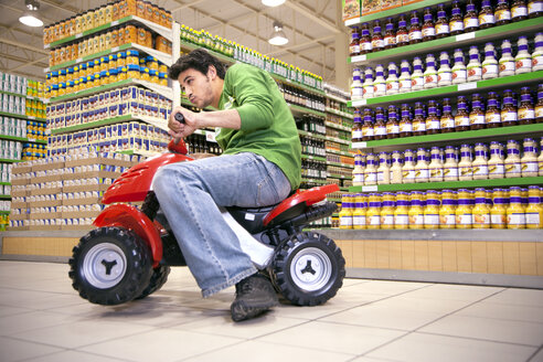 Man driving with toy car in a supermarket - RMAF000237