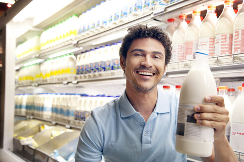 Portrait of smiling man sitting in front of fridge in a supermarket holding milk bottle - RMAF000246