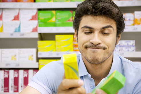 Portrait of a man in a supermarket comparing two products - RMAF000249