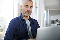 Mature man working from home using laptop - FKF001542
