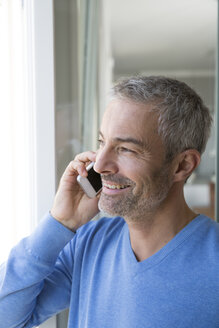 Mature man working from home using smart phone - FKF001563