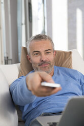 Mature man sitting on couch with laptop, using remote control - FKF001578