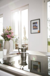 Bunch of flowers and coffee maker on oven in kitchen block - FKF001593
