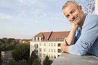 Mature man on balcony, enjoying the view - FKF001599