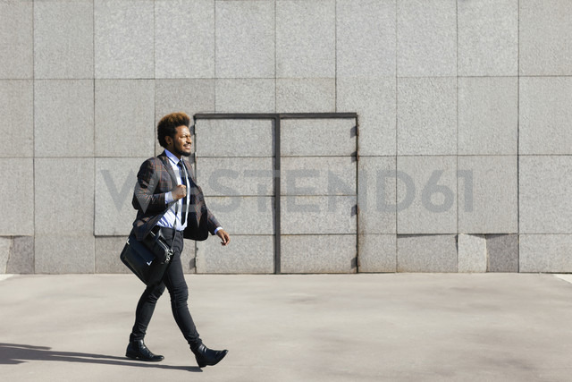 Young businessman walking outdoors - EBSF001082
