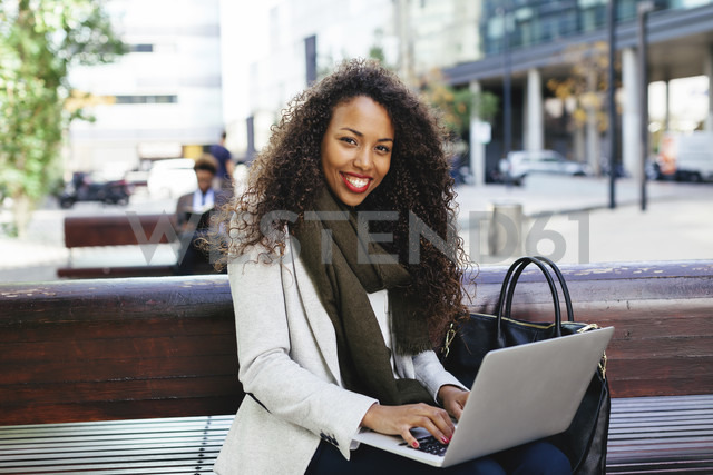 Smiling young woman using laptop on bench - EBSF001097