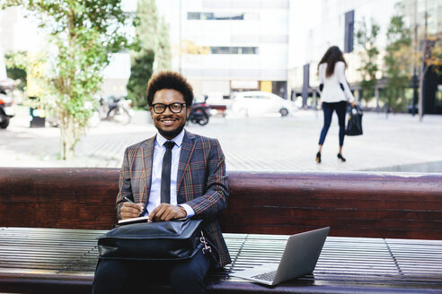 Smiling young businessman with laptop and notebook on bench - EBSF001100