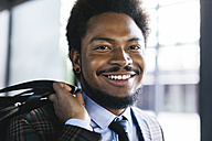 Portrait of smiling young businessman carrying a bag - EBSF001112
