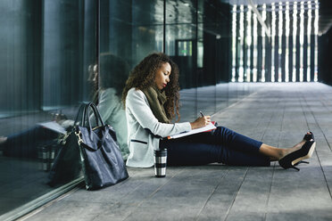 Young businesswoman sitting outdoors writing in folder - EBSF001127