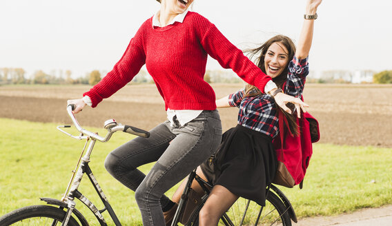 Two exuberant young women sharing a bicycle in rural landscape - UUF006041