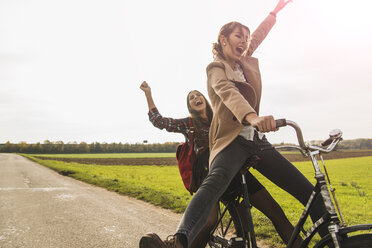 Two exuberant young women sharing a bicycle in rural landscape - UUF006044
