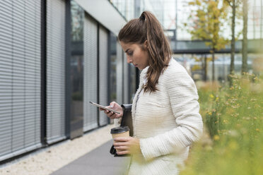 Young businesswoman outdoors looking at cell phone - UUF006056