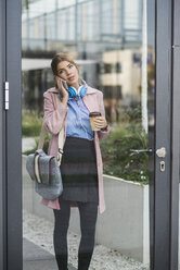 Young woman on cell phone holding coffee to go - UUF006068