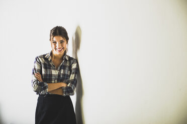Smiling brunette woman standing at a wall - UUF006104