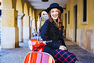 Italy, Verona, happy young woman with scooter - GIOF000525