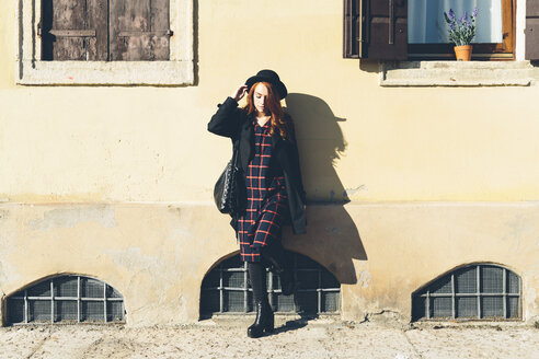 Italy, Verona, young woman leaning against house wall - GIOF000528