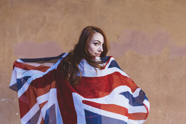 Smiling woman holding a British flag - GIOF000534