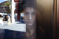 Portrait of young woman behind window pane - GIOF000543