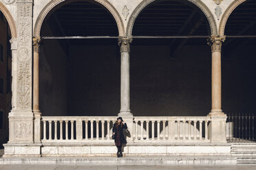 Italy, Verona, young woman in front of an ancient building - GIOF000546