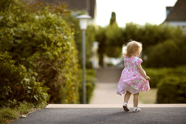 Back view of blond little girl wearing dress with floral design - NIF000049