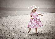 Happy blond little girl wearing hat and summer dress with floral design  dancing on pavement - NIF000052