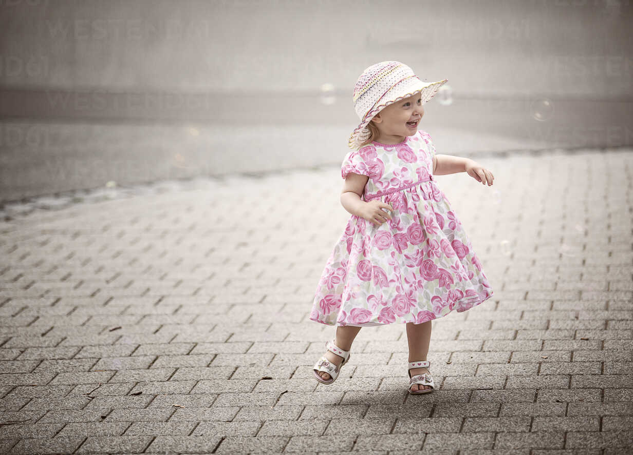Happy blond little girl wearing hat and summer dress with floral design  dancing on pavement - NIF000052 - Nailia Schwarz/Westend61