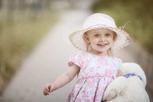 Portrait of smiling blond little girl wearing hat and summer dress with floral design - NIF000055