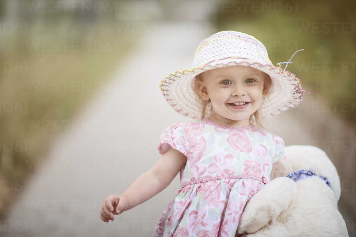 Portrait of smiling blond little girl wearing hat and summer dress with floral design - NIF000055 - Nailia Schwarz/Westend61