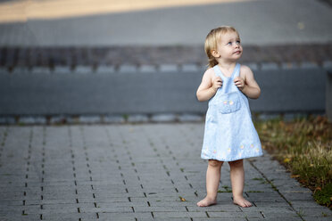 Barefoot blond little girl standing on pavement looking up - NIF000064