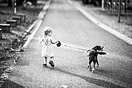 Back view of little girl walking along the street with her dog - NIF000067