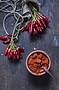 Bunches of red chili peppers and bowl with chili powder on wood - SBDF002413