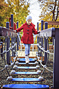 Girl walking on bridge on playground - VTF000485