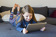 Smiling girl lying on the couch using digital tablet - SARF002313