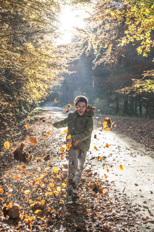 Boy playing with leaves in autumnal forest - DEGF000588